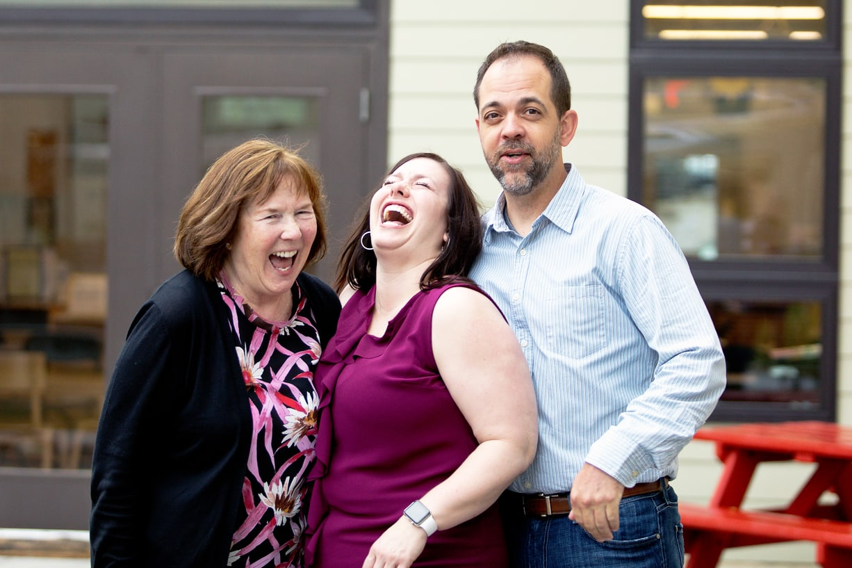 Group of three people laughing and smiling