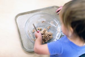 Toddler mixing with spoon and bowl